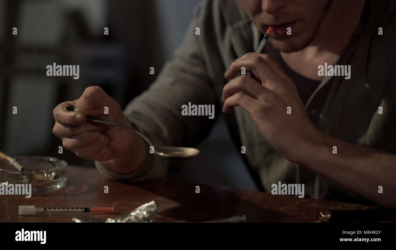 Junkie holds heroin dose in spoon and prepares syringe for injection, close up - Stock Image