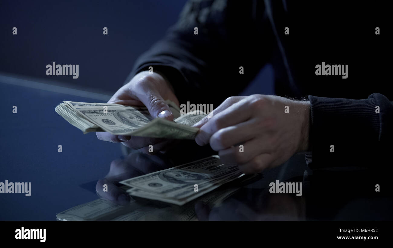 Male hands counting dollars, black salary, money laundering, illegal business - Stock Image