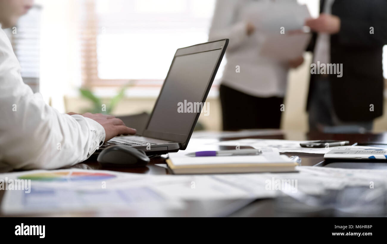 Worker taking notes on laptop while two colleagues discussing papers at office - Stock Image
