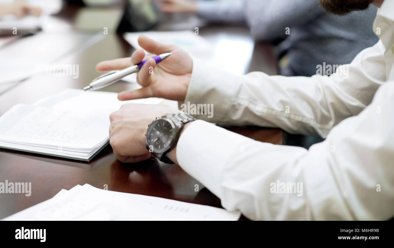 Bored employee sitting at business conference and spinning pen in his hand Stock Photo