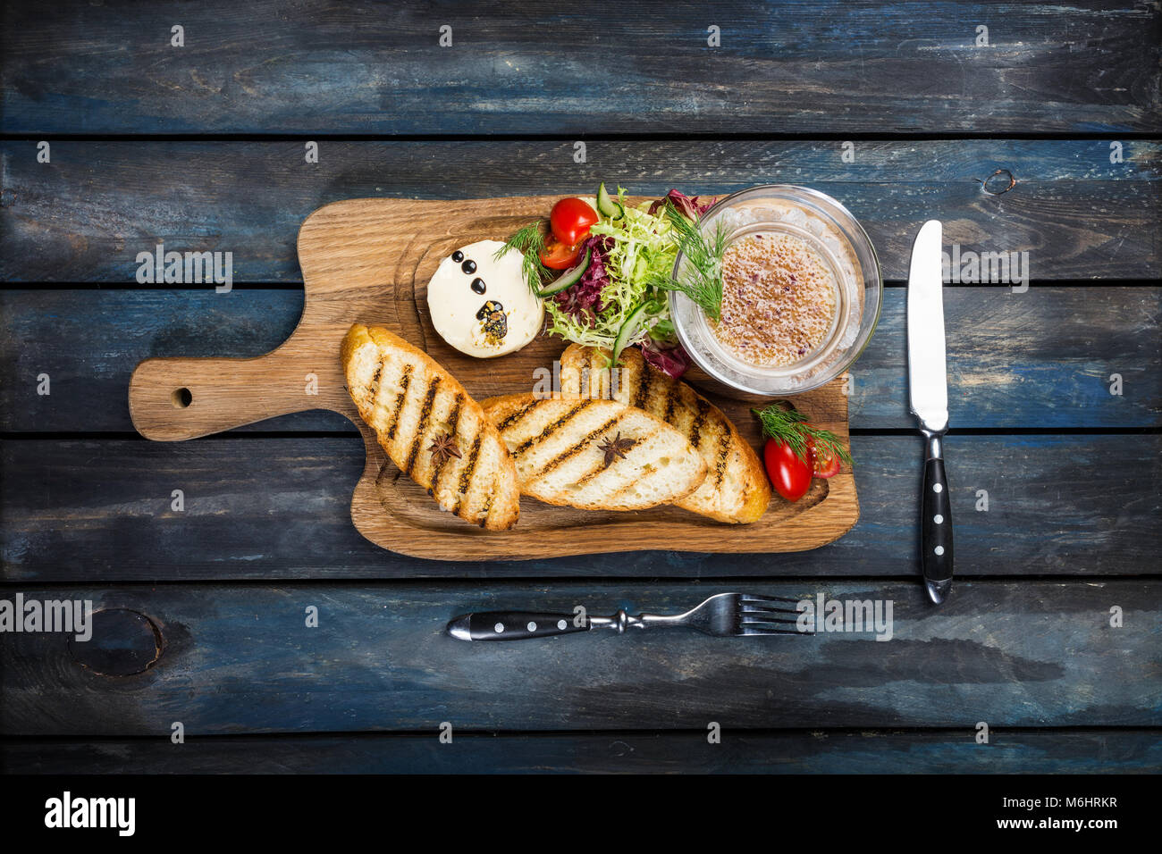 Toast with butter and caviar served with cutlery on a wooden background - Stock Image