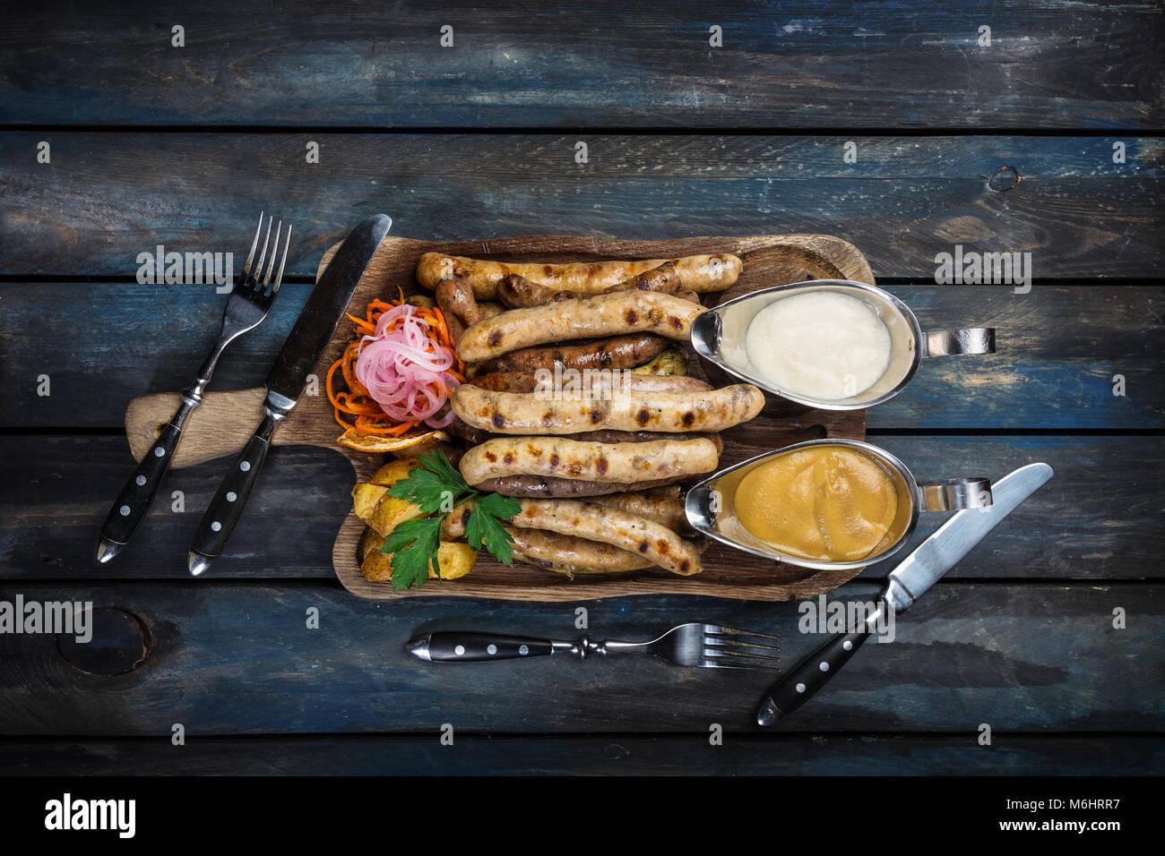 Smoked sausage with sauerkraut and potato wedges. - Stock Image