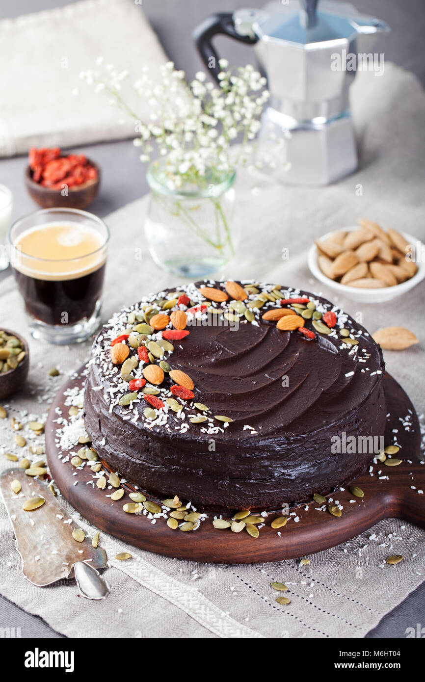 Vegan chocolate beet cake with avocado frosting, decorated with nuts and seeds. - Stock Image
