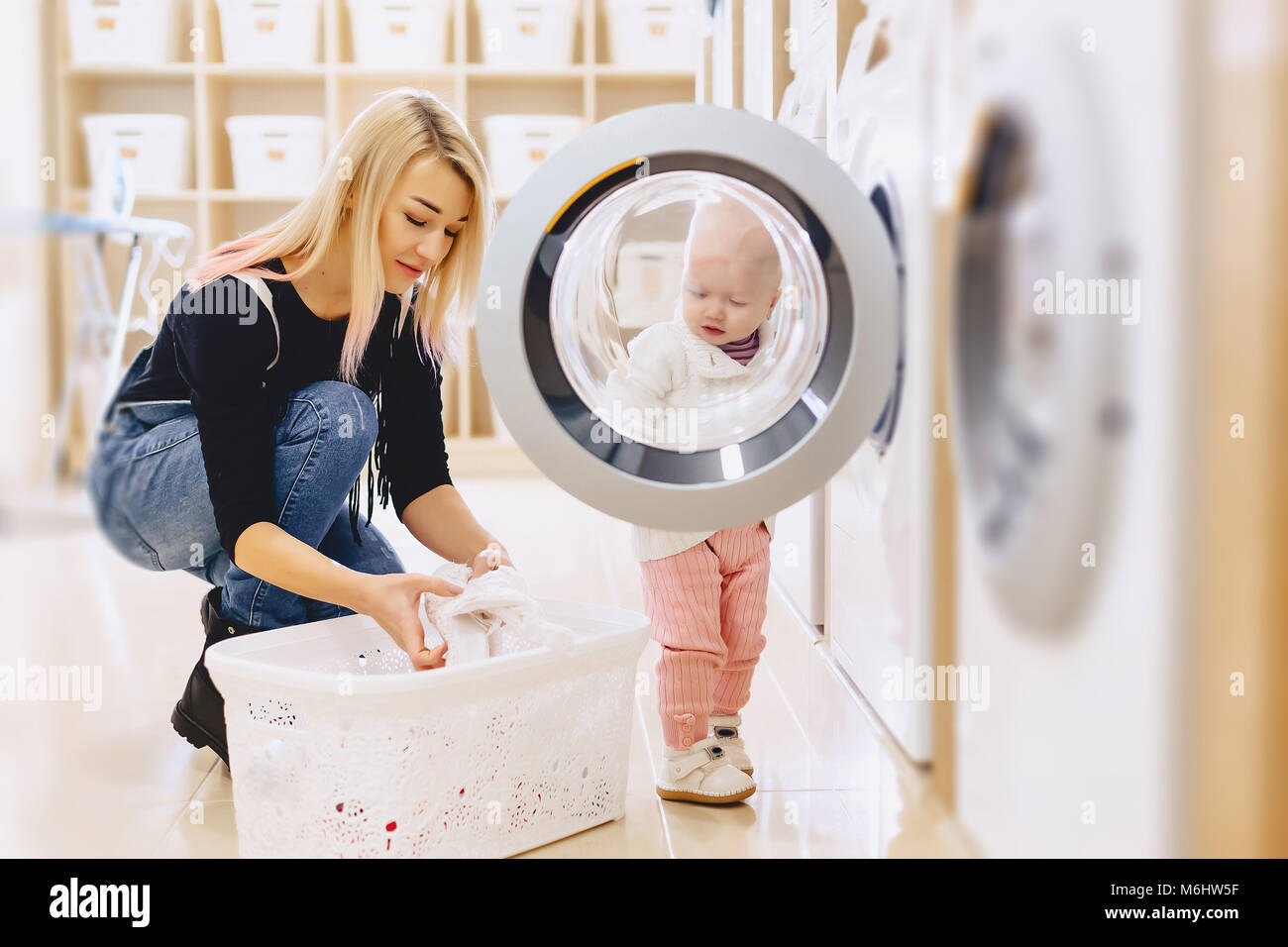 Mom and baby in the laundry take things and play fun games Stock Photo