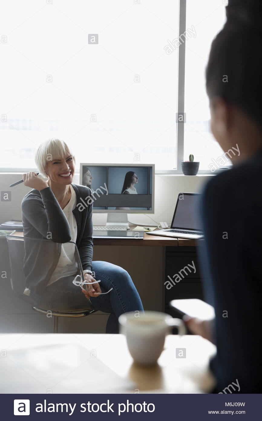 Female photo editor at computer talking to colleague - Stock Image