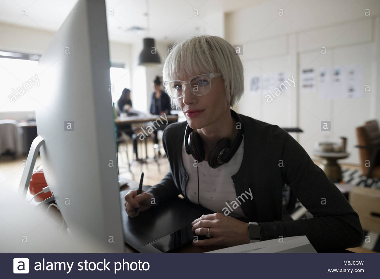 Focused female graphic designer using graphics tablet, leaning toward computer in office - Stock Image