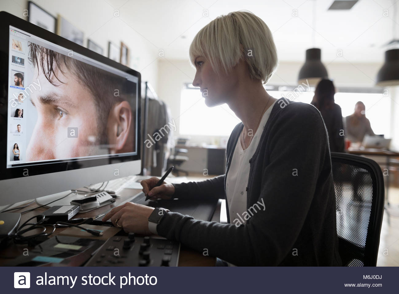 Female photo editor using graphics tablet, editing digital photograph on computer in office - Stock Image