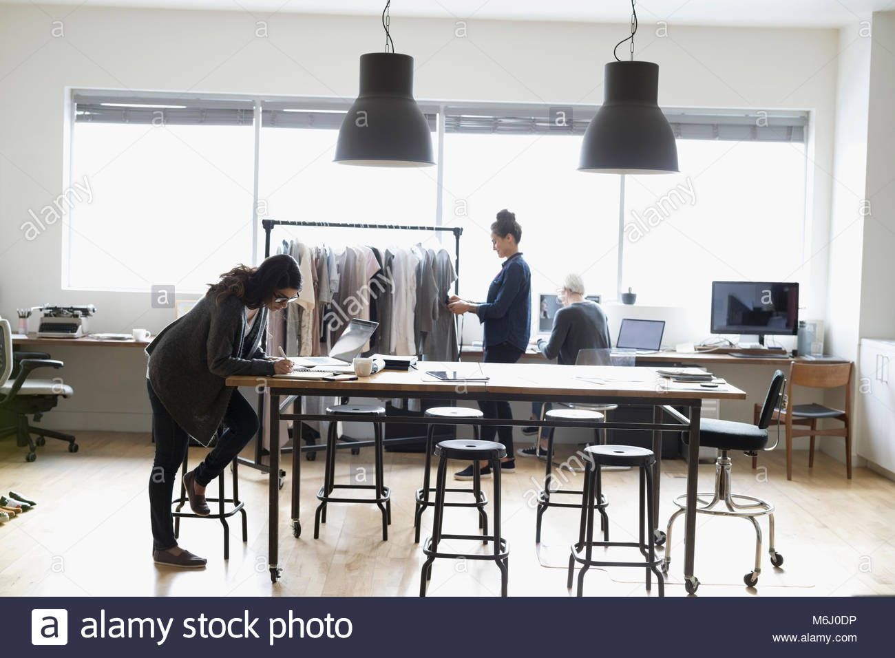 Production assistants and wardrobe stylist working in office - Stock Image