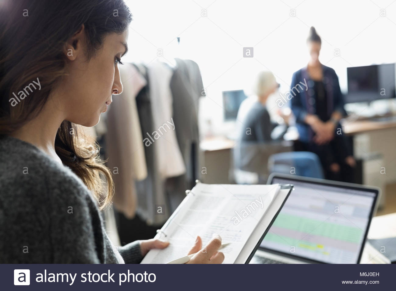 Female production manager reviewing schedule in office - Stock Image