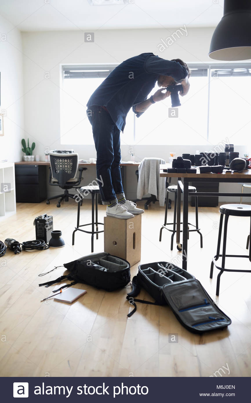 Male photographer standing on box, using digital camera in office - Stock Image