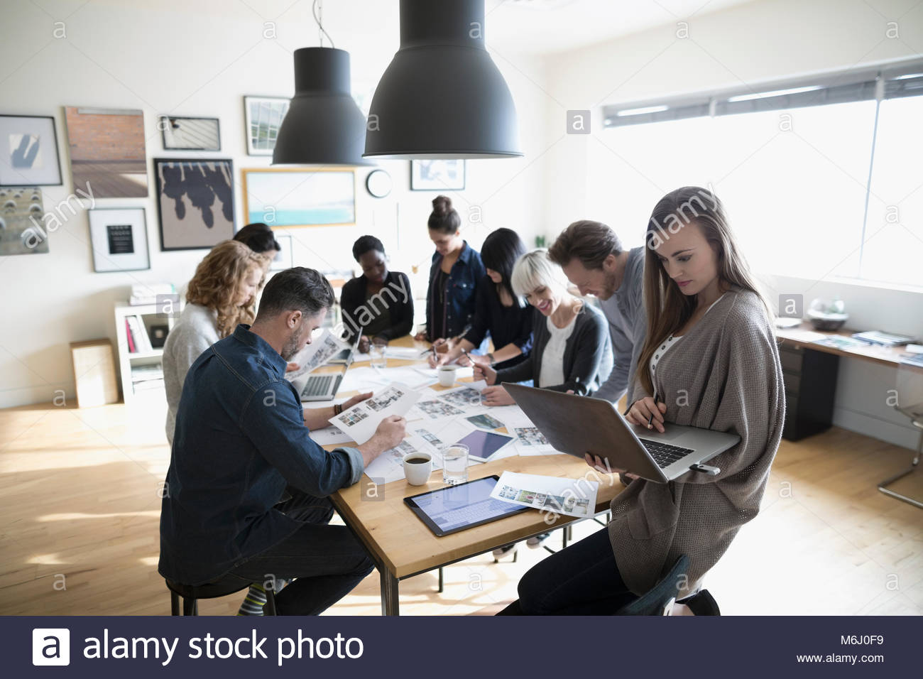 Production team reviewing photo proofs in office meeting - Stock Image