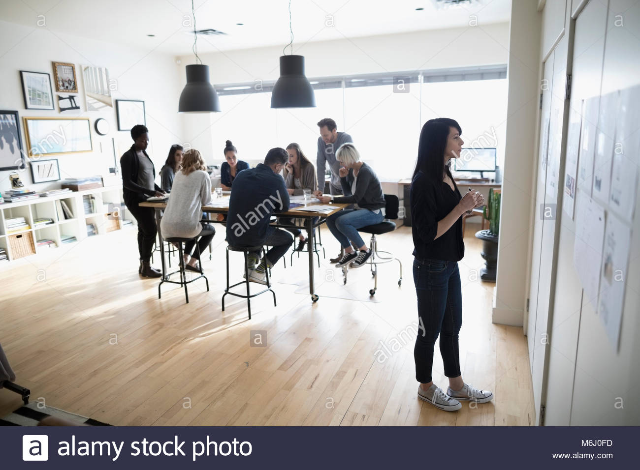 Female photo editor reviewing photo proofs hanging on office wall - Stock Image