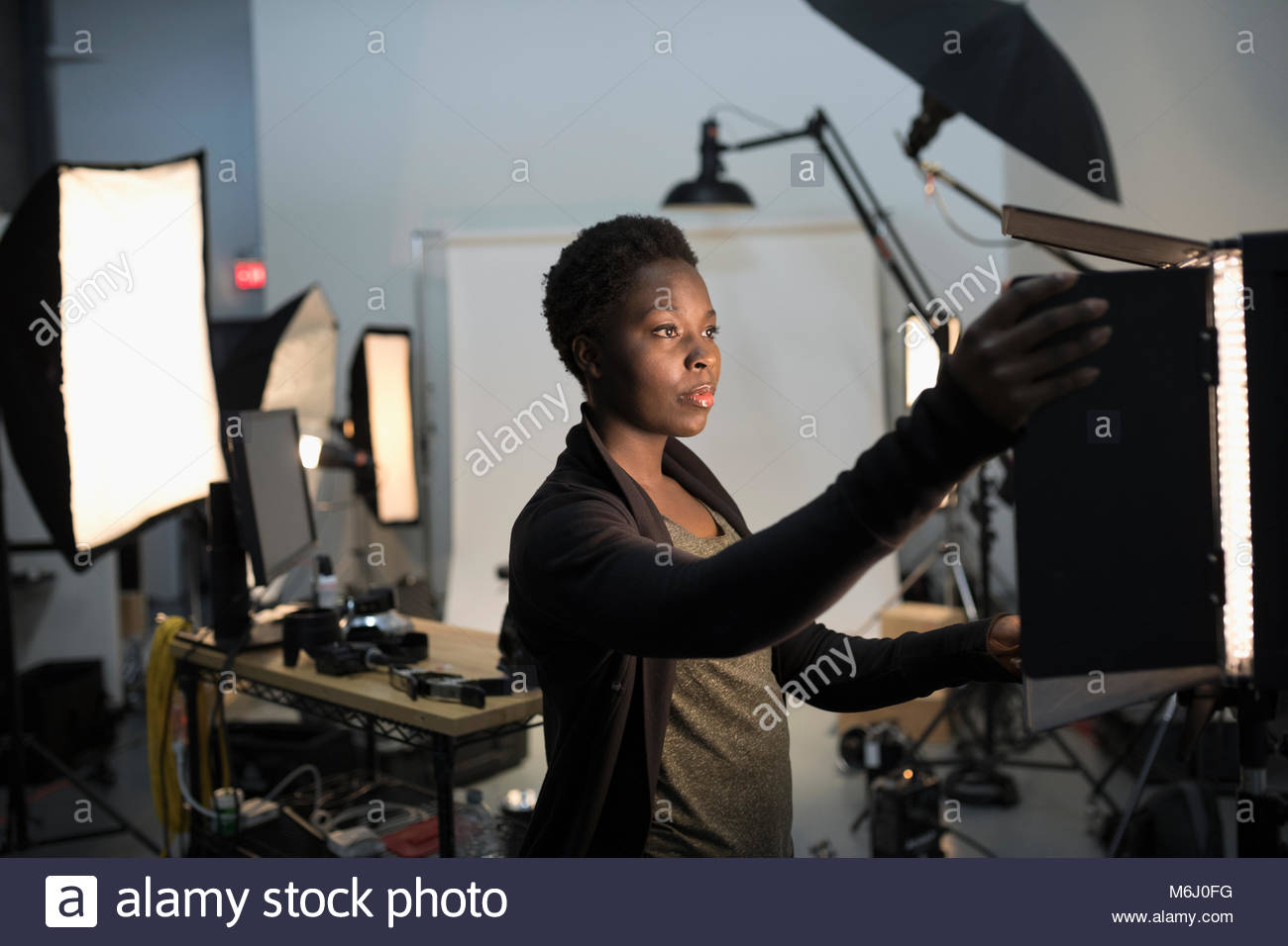 Focused female photographer adjusting lighting equipment for photo shoot in studio - Stock Image
