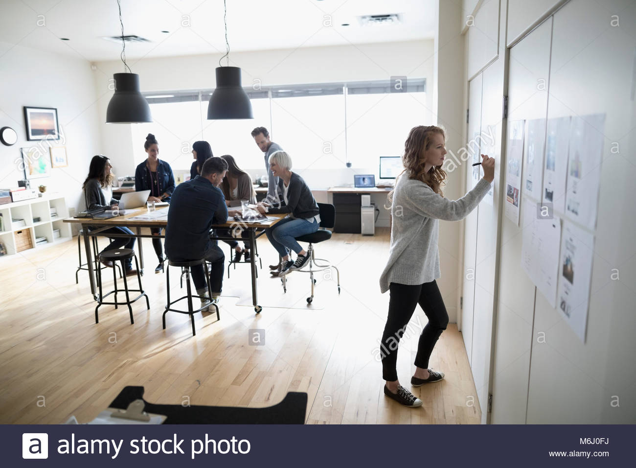 Female photo editor with digital tablet editing photo proofs hanging on office wall - Stock Image