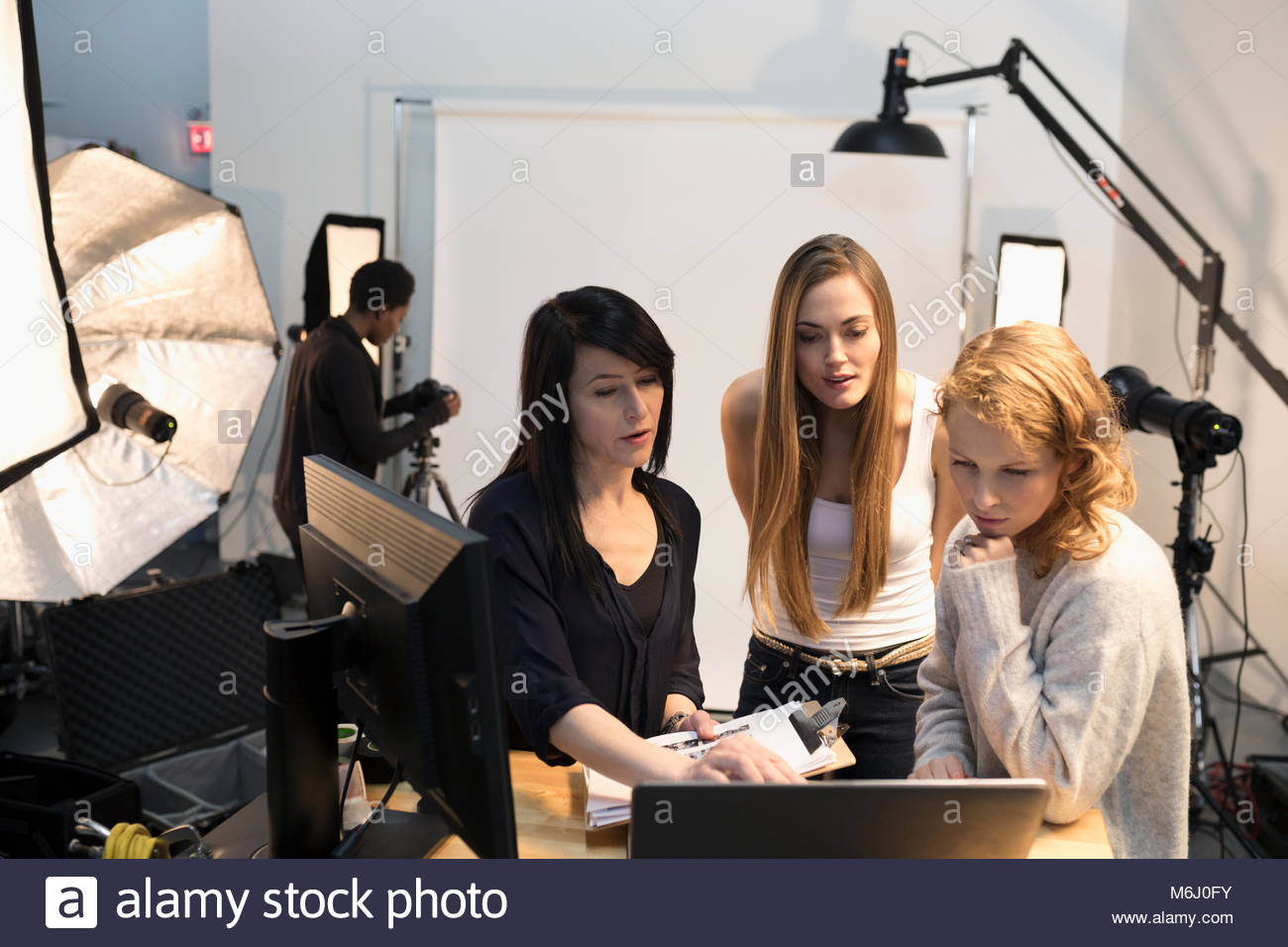 Female production assistants and model at laptop at photo shoot in studio - Stock Image
