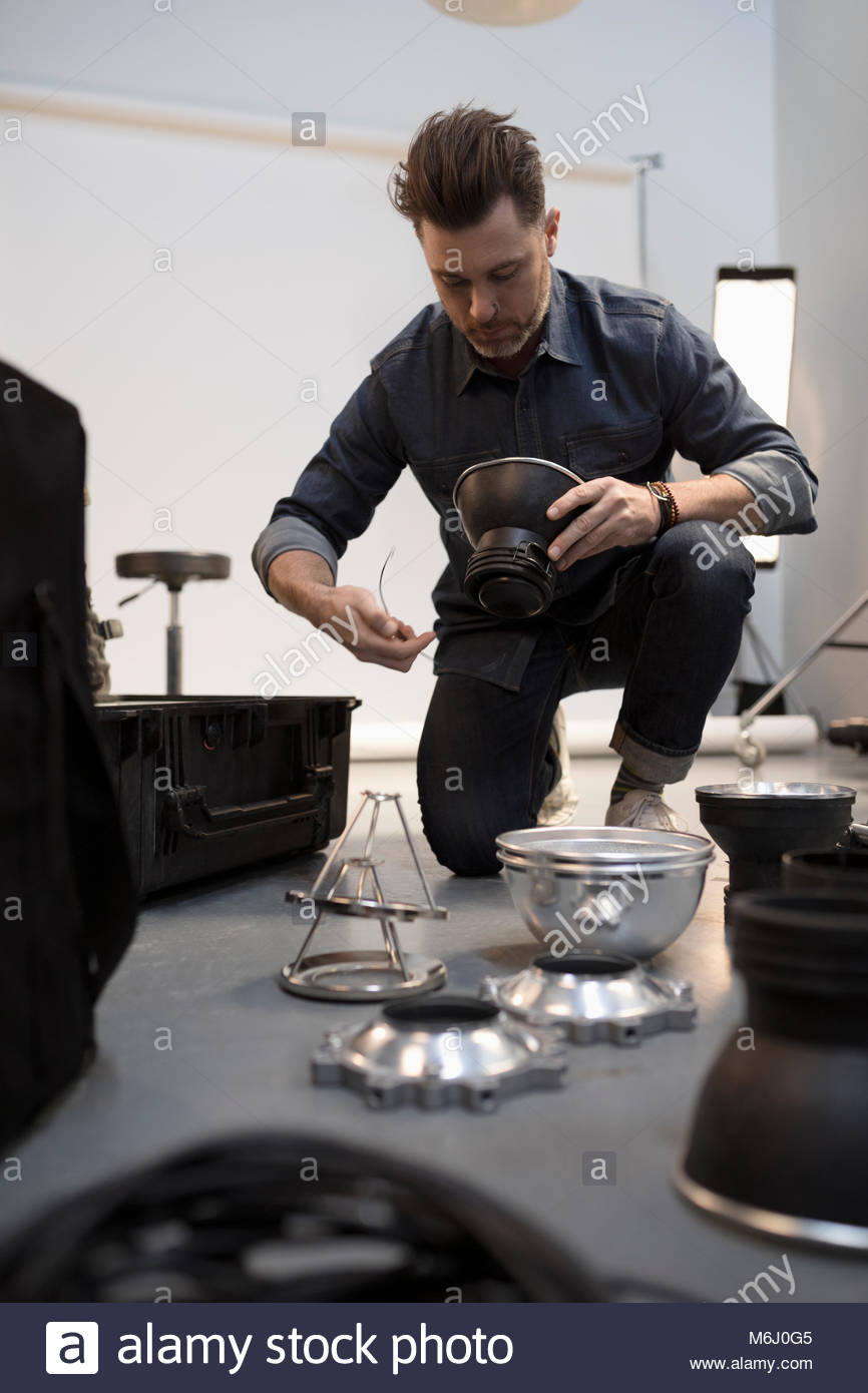 Male photographer preparing lighting equipment for photo shoot in studio - Stock Image