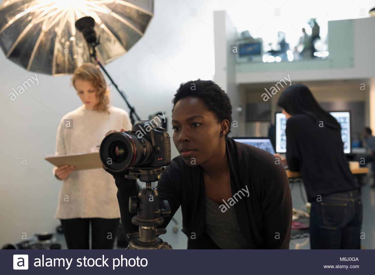 Focused female photographer using digital camera at photo shoot in studio Stock Photo