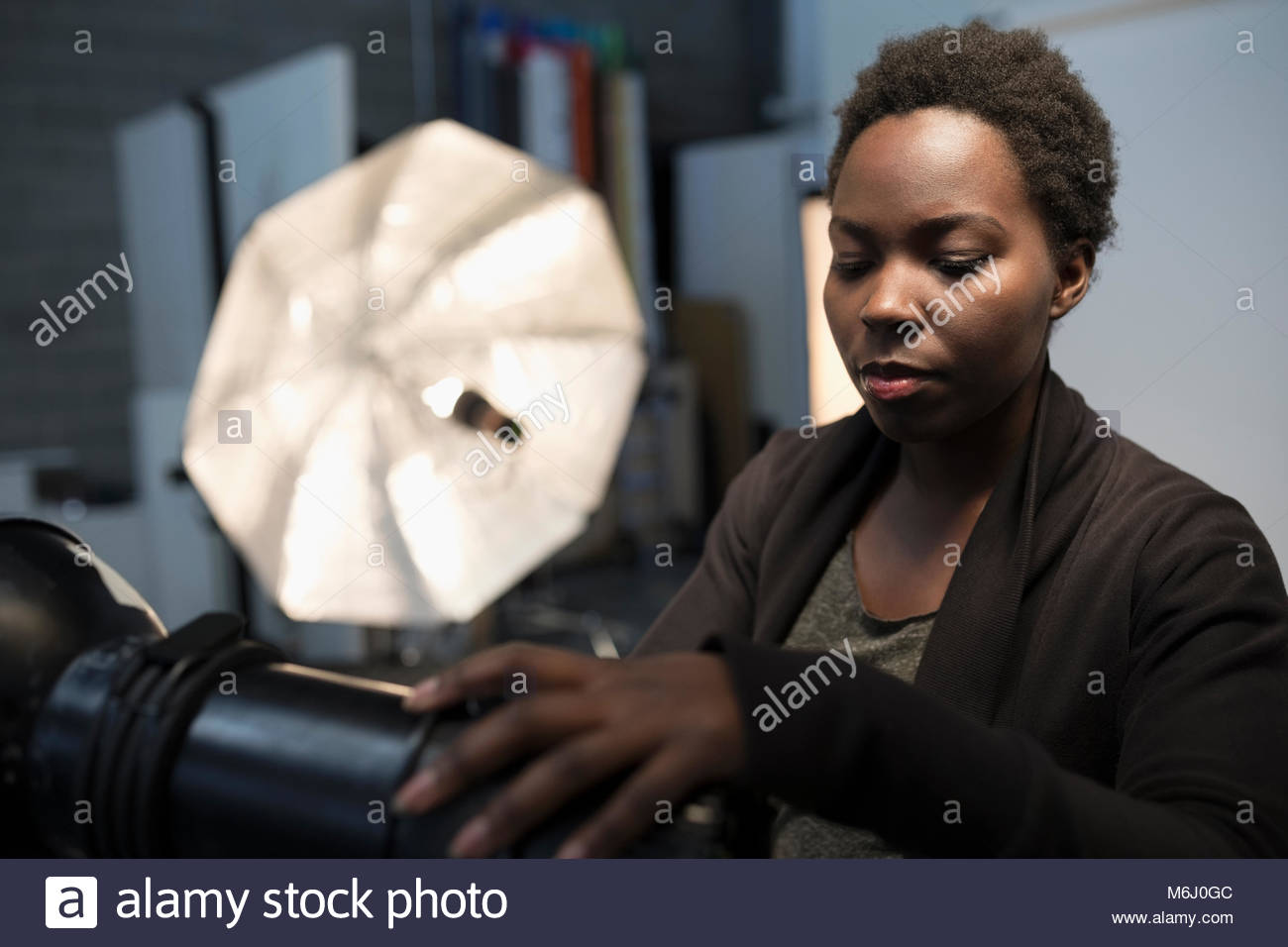 Focused female photographer preparing lighting equipment for photo shoot in studio - Stock Image