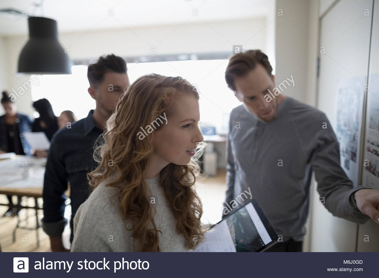 Photo editors with digital tablet discussing photo proofs hanging on office wall - Stock Image