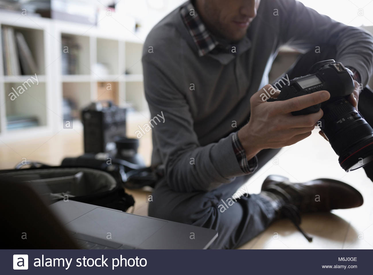 Male photographer using digital camera at laptop on floor - Stock Image