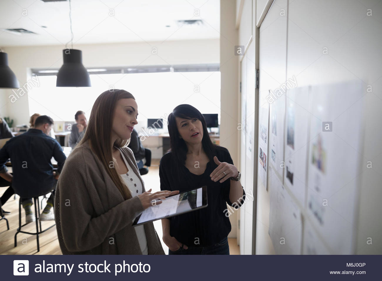Female photo editors with digital tablet discussing photo proofs hanging on office wall - Stock Image