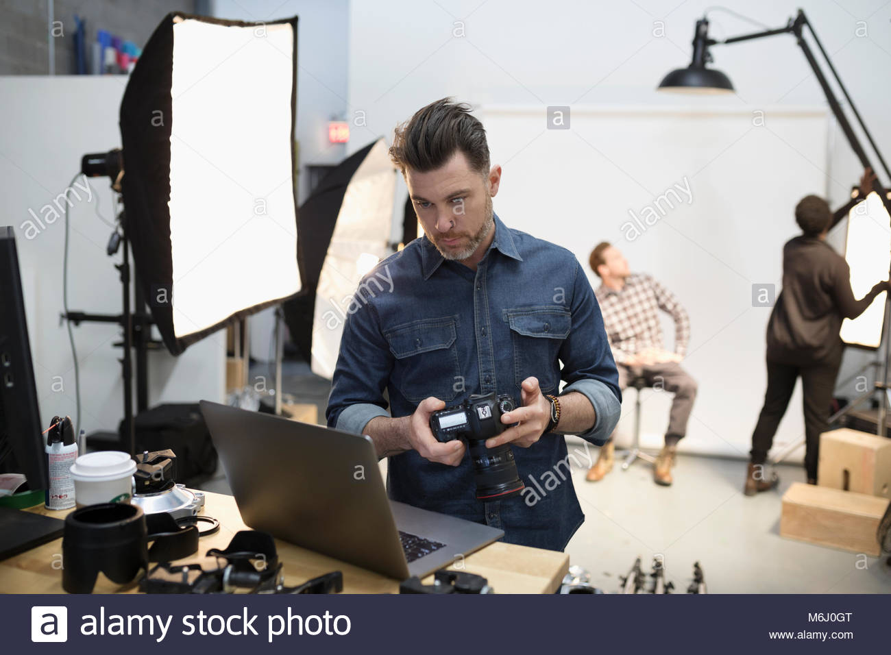 Male photographer with digital camera using laptop at photo shoot in studio - Stock Image