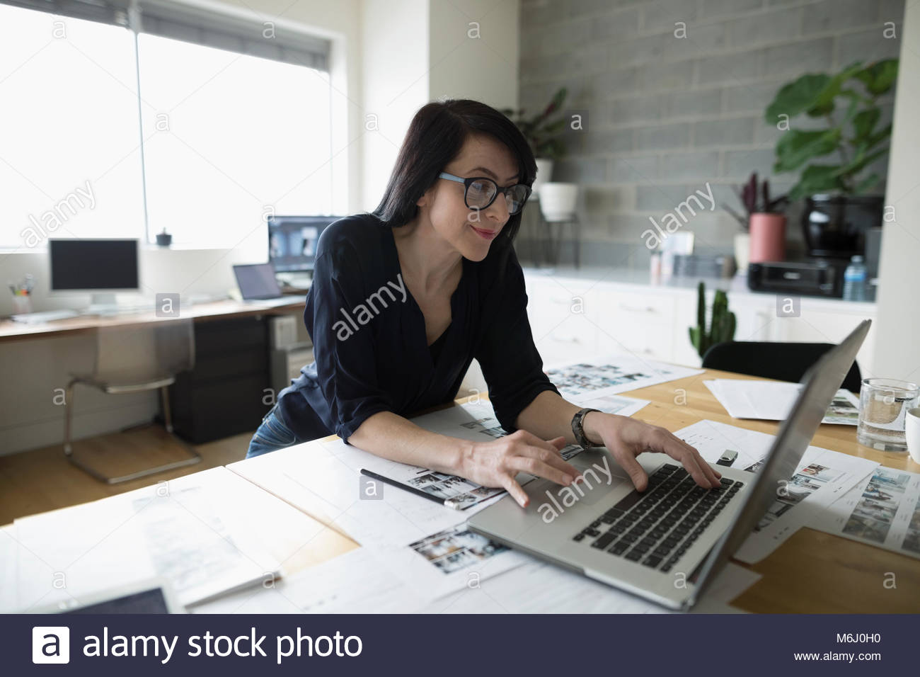 Female photo editor working at laptop, reviewing photo proofs in office Stock Photo