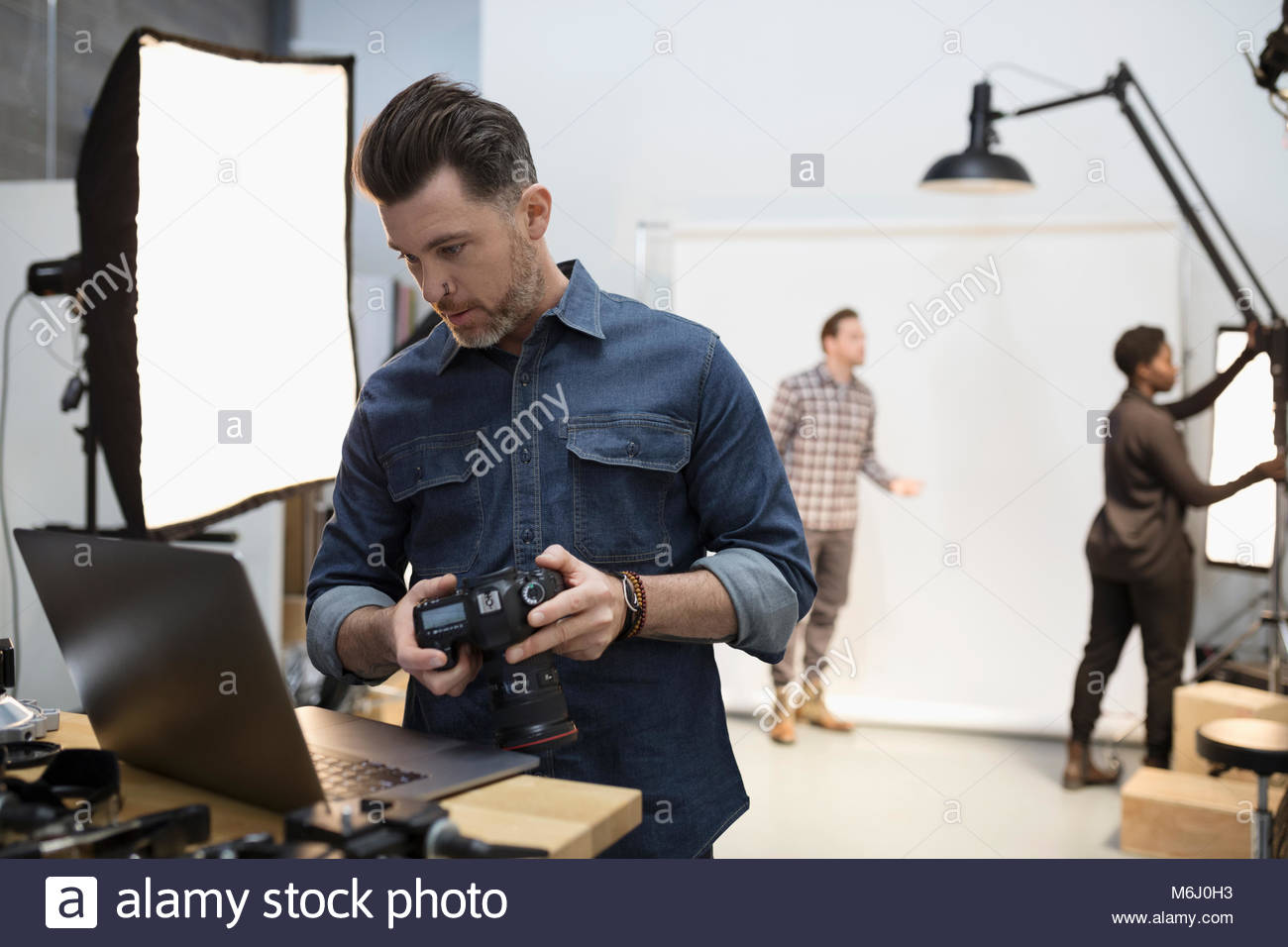 Male photographer with digital camera using laptop at photo shoot in studio Stock Photo