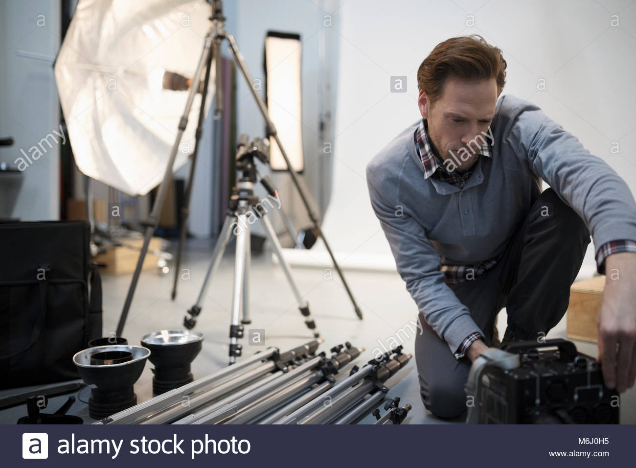 Male photographer preparing equipment for photo shoot in studio - Stock Image