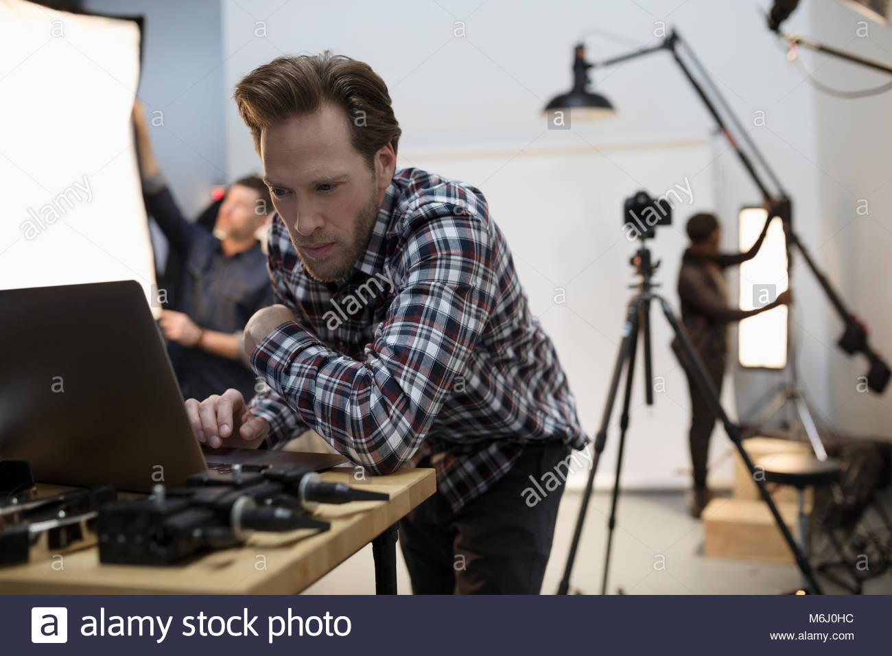 Male production manager using laptop at photo shoot in studio - Stock Image