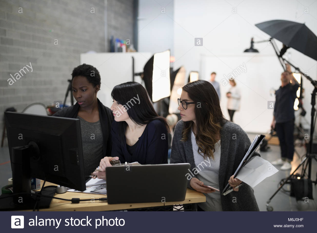 Female production assistants using computer and laptop at photo shoot in studio Stock Photo