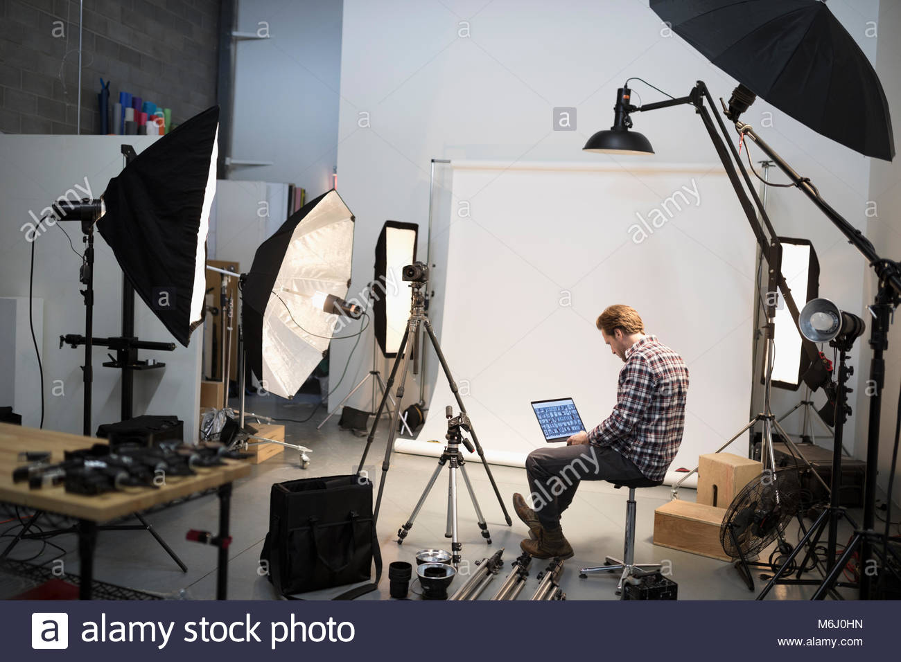 Male photographer reviewing digital photo proofs on laptop at photo shoot in studio - Stock Image