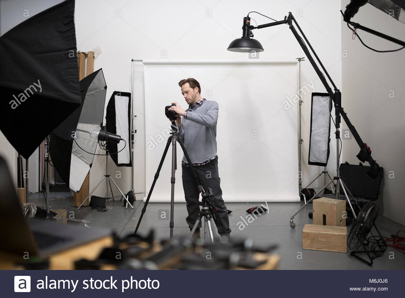 Male photographer preparing digital camera equipment for photo shoot in studio - Stock Image