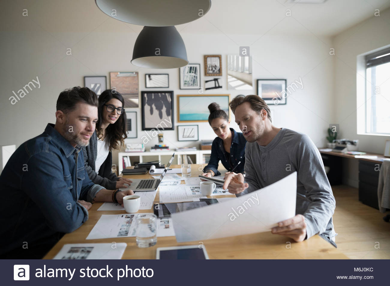 Photo editor production team reviewing photo proofs in office meeting - Stock Image