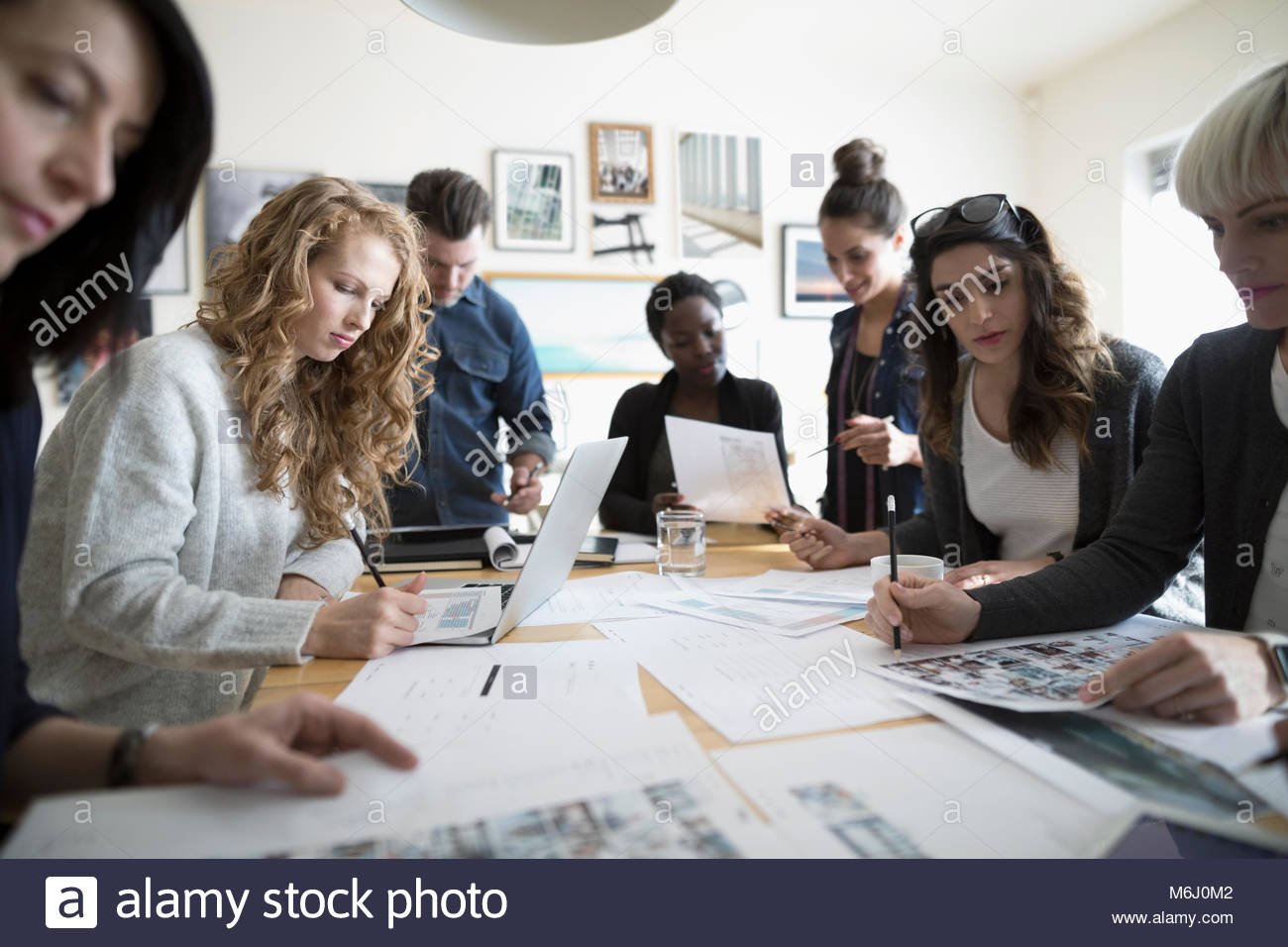 Production team editing photo proofs in office meeting - Stock Image
