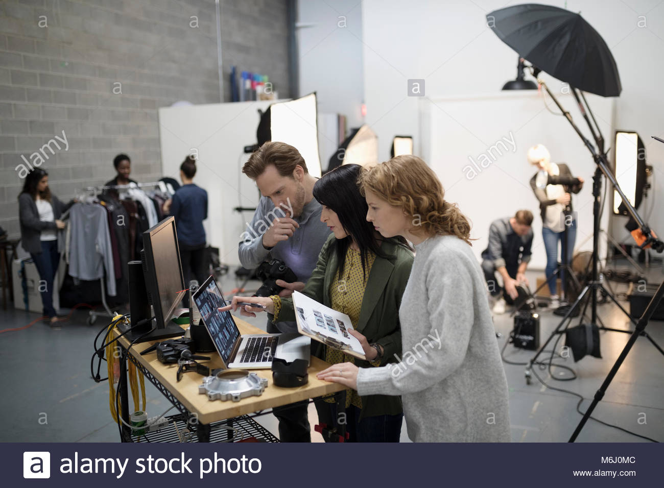 Photographer and production team preparing photo shoot in studio - Stock Image