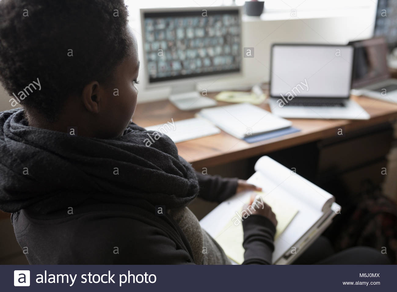 Female photo editor brainstorming, writing in office - Stock Image