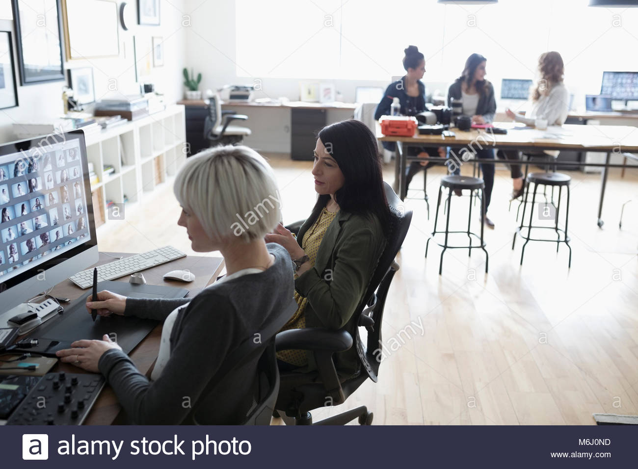 Female photo editors with graphics tablet editing digital photo proofs on computer in office - Stock Image