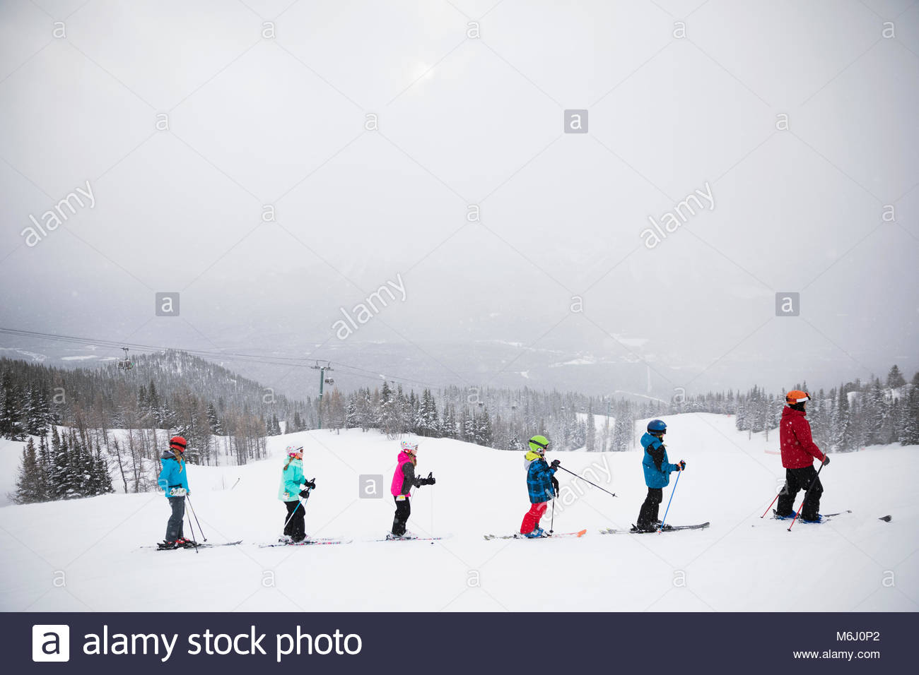Kids following ski instructor during ski lesson on snowy mountain - Stock Image