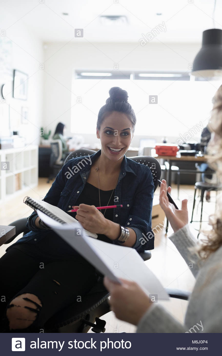 Smiling female designer with paperwork listening to colleague in office - Stock Image