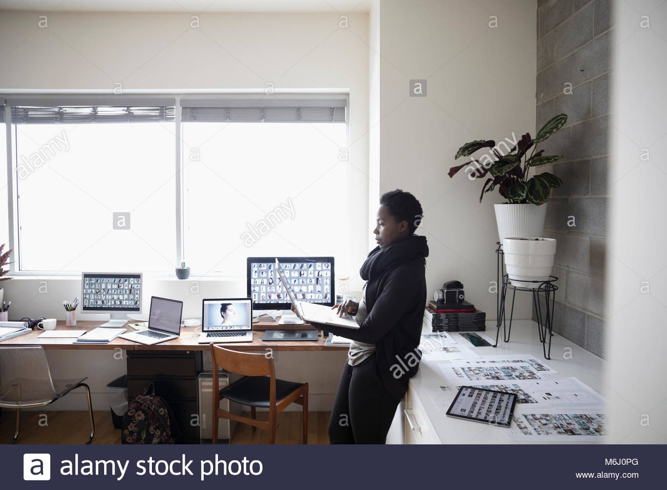 Female photo editor using laptop in office - Stock Image