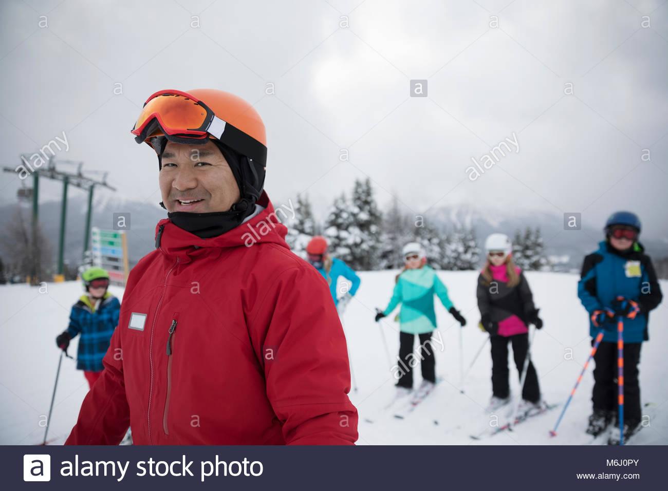 Portrait smiling, confident ski instructor teaching kids on snowy mountain - Stock Image