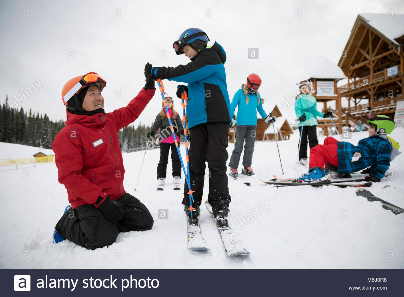 Ski instructor and boy high-fiving during ski lesson at ski resort - Stock Image