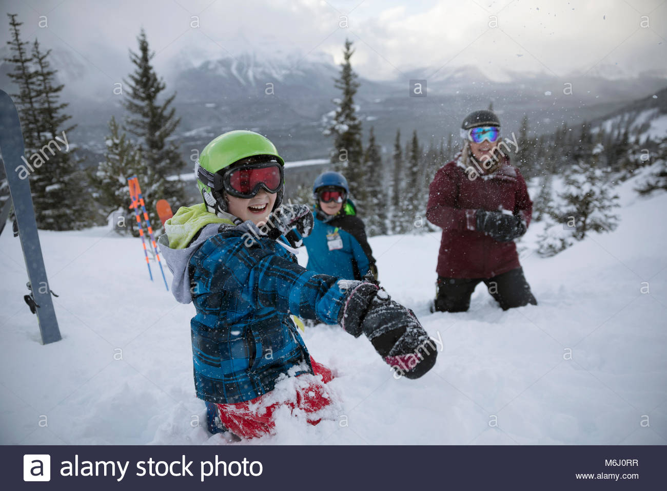 Portrait playful boy skier enjoying snowball fight with family on snowy mountain - Stock Image