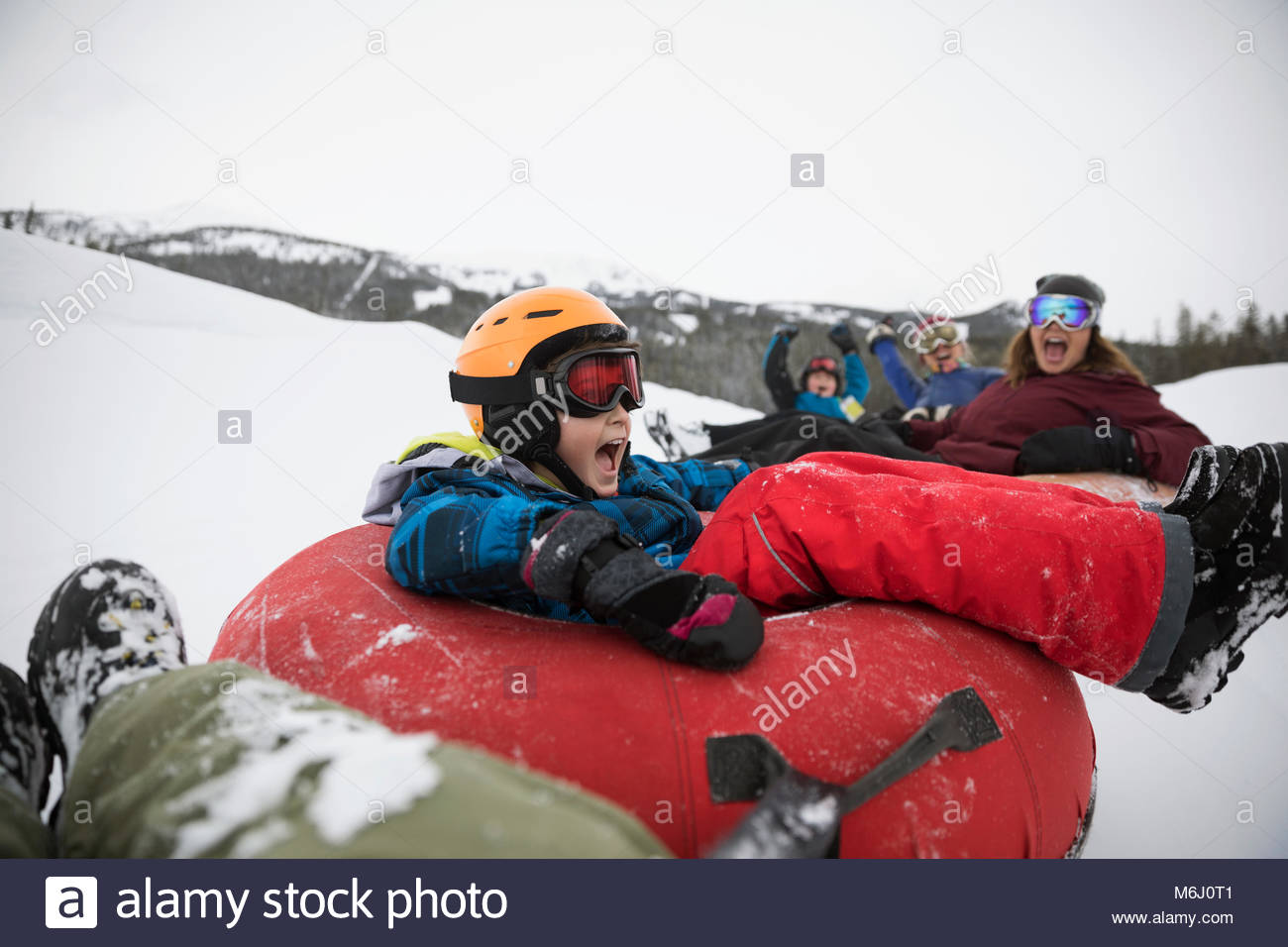 Playful boy inner tubing with family in snow at tube park - Stock Image