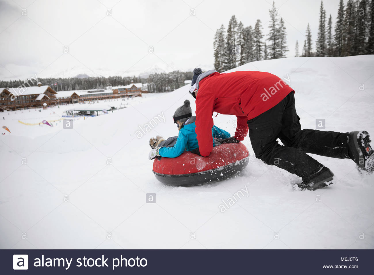 Father pushing daughter in inner tube in snow at tube park - Stock Image