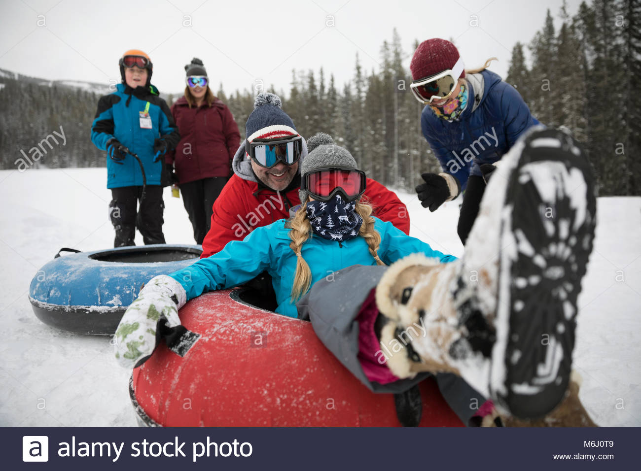 Portrait playful family inner tubing in snow at tube park - Stock Image