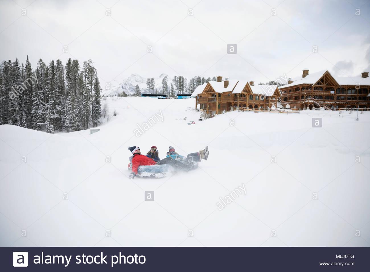 Playful family inner tubing in snow at ski resort tube park - Stock Image