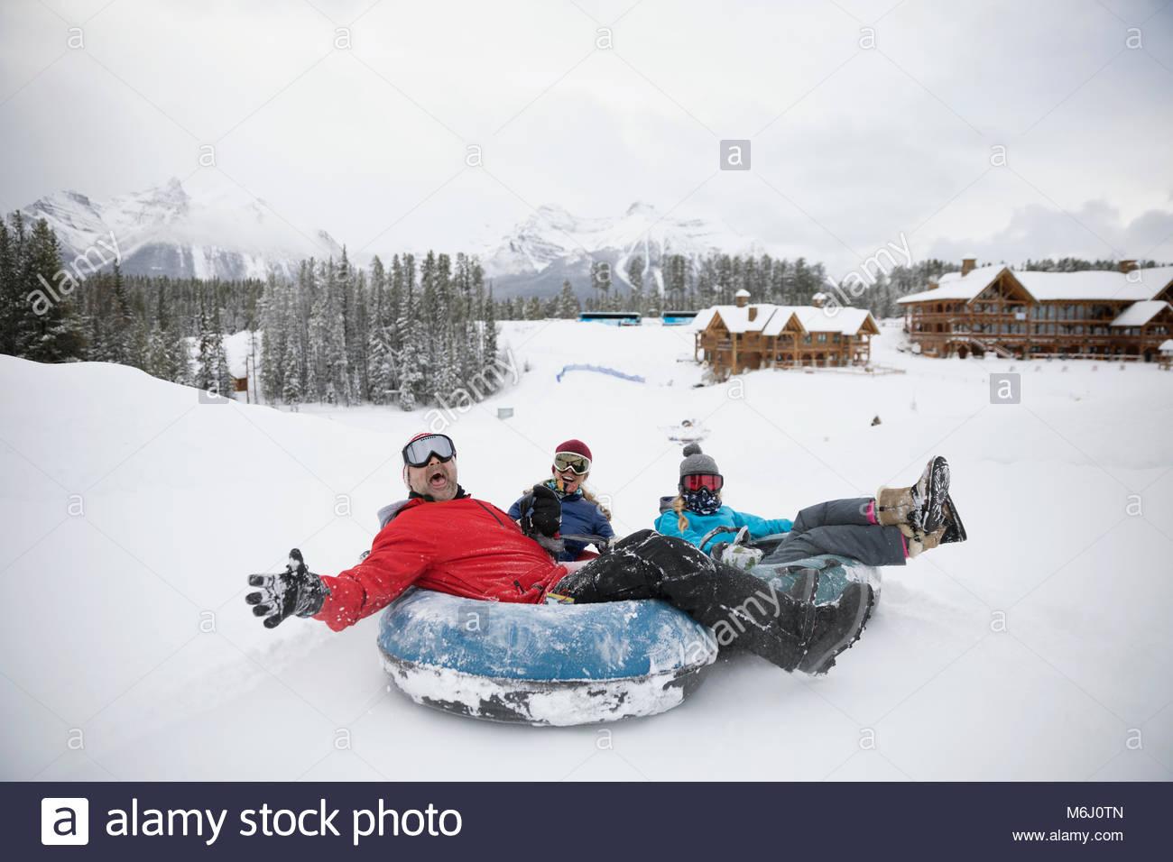 Portrait playful family inner tubing in snow at ski resort tube park - Stock Image