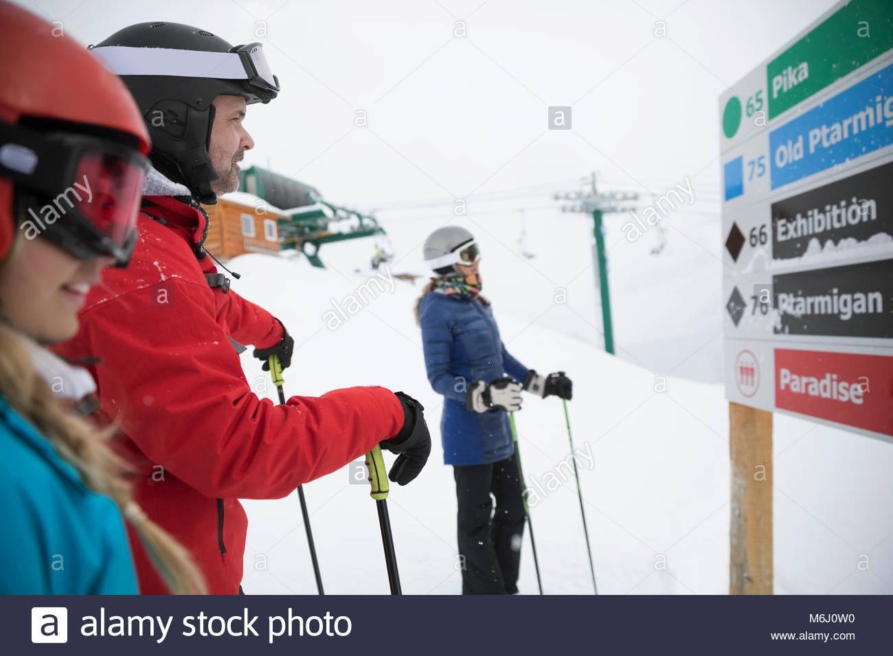Family snowshoeing, looking at ski resort map - Stock Image